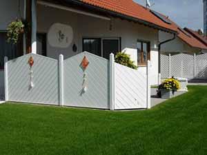 Geschlossene Sichtschutzwand auf einer Terrasse mit senkrechten Aluminiumpfosten und weißen Abdeckkappen.