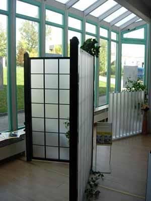 In unserer Ausstellung: Rankgitter mit satiniertem Glas, im Hintergrund ein Gartenzaun aus Aluminium.