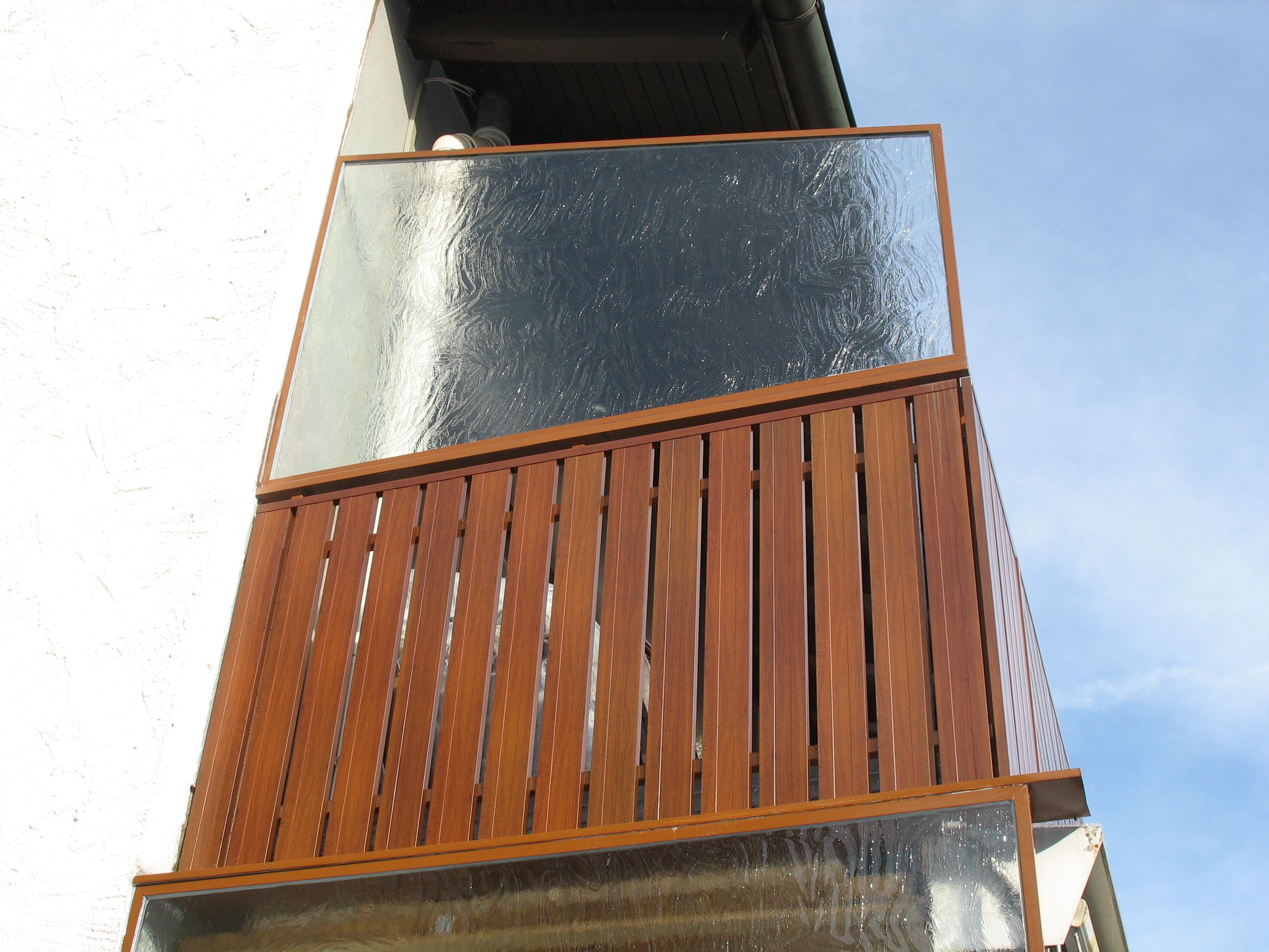 Balkonverkleidung IDEA in Holzoptik mit Windschutz auf dem Handlauf