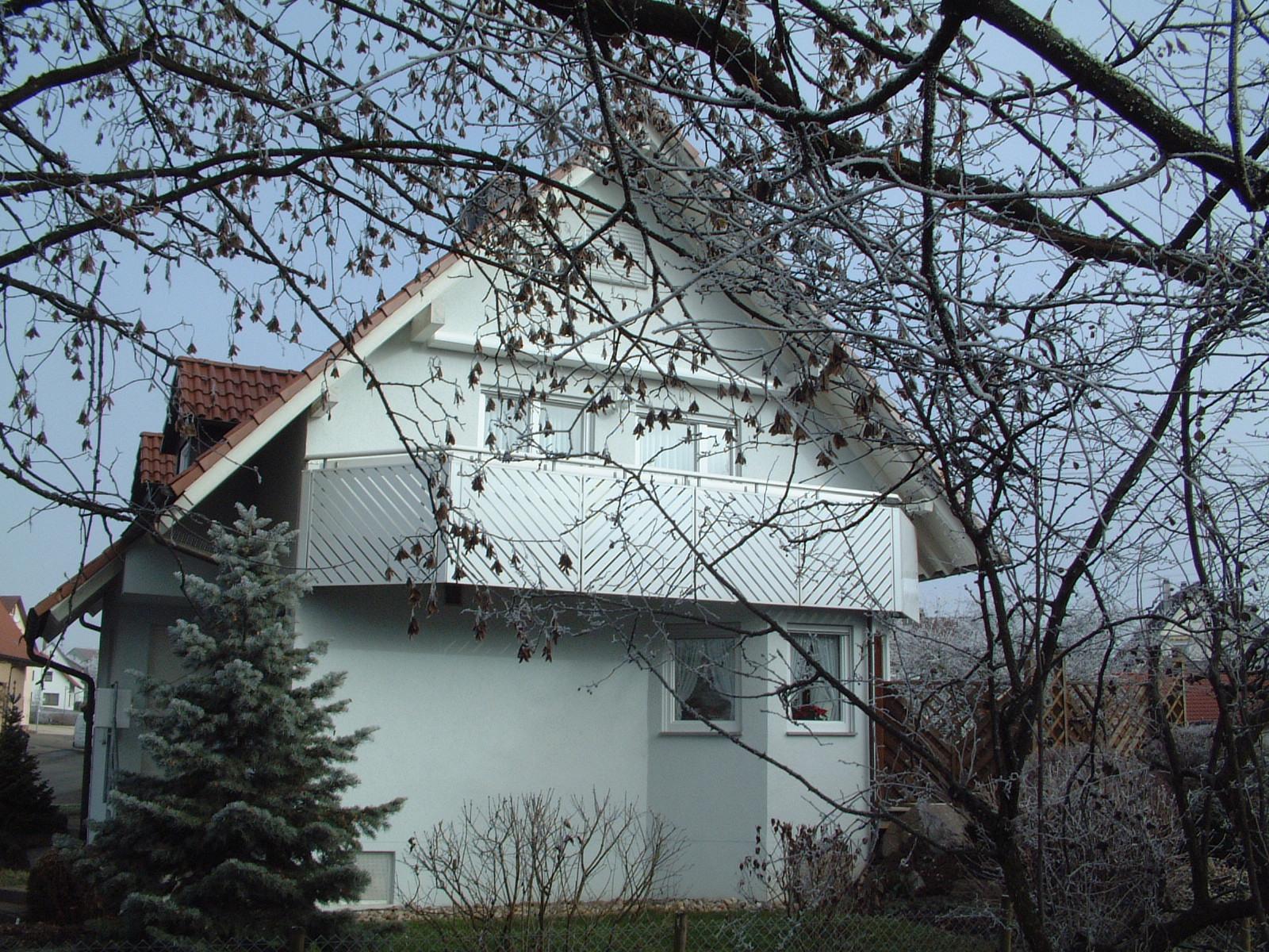 Handlauf und Balkonverkleidung aus weißem, pulverbeschichtetem Aluminium.